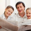 Family reading a newspaper — Stock Photo #8481933