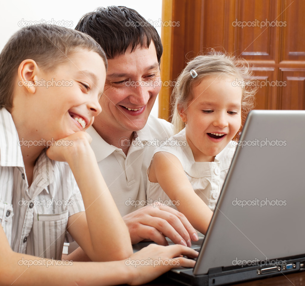 Happy family with laptop. Father with children play in the computer  Stock Photo #8481976