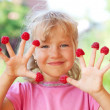 Little girl with raspberry — Stock Photo #8703940