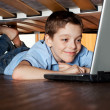 Child playing laptop under the bed — Stock Photo