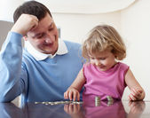 Dad and daughter puts coins — Stock Photo