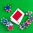 Counters and playing cards on a green background — Stock Photo