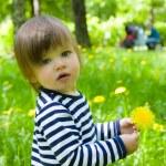 Toddler girl holding yellow flower dandelions — Stock Photo #9655618