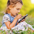 Little girl writes stylus on device — Stock Photo #10023176