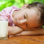 Постер, плакат: Little girl sleeps around glass of milk