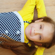 Stock Photo: Little girl in yellow dress lying on floor