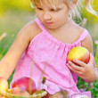 Little blonde girl sitting on grass with apples — Stock Photo