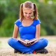 Teenage girl sitting and reading a book — Stock Photo