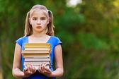 Dospívající dívka drží zásobníku sedmi knih — Stock fotografie