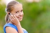 Smiling teenager girl in talking on cell phone — Stock Photo