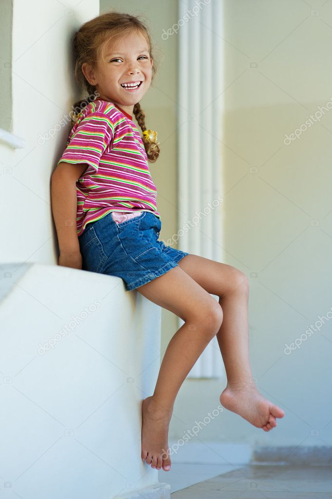 Little girl in shorts sitting — Stock Photo ...