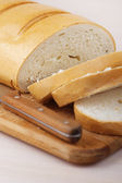 Cut loaf of white bread and knife — Stock Photo