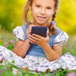 Little girl writes stylus on device — Stock Photo