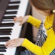 Little girl in yellow dress plays piano - Zdjęcie stockowe