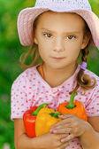 Little girl in hat holding pepper — Stock Photo