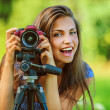 Beautiful woman photographed with camera tripod — Stock Photo