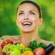 Woman with bare shoulders holding fruit and vegetables - Stockfoto