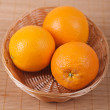 Three in wicker basket of oranges - Stock Photo