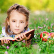 Little girl lies on grass with apples and book — Stock Photo