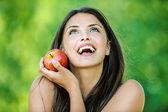 女性の赤いリンゴを保持していると笑みを浮かべて — ストック写真