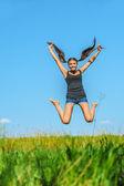 Beautiful woman jumps high into sky — Stock Photo