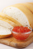 Cut loaf of white bread and caviar — Stock Photo