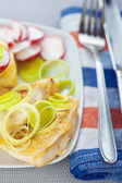 Fried fish with onions and radishes — Stock Photo
