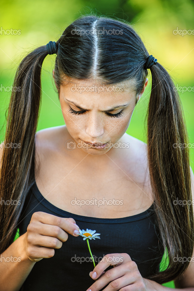 Portrait of young beautiful woman wonders, tearing petals on daisy, on green background summer nature. — Stock Photo #10378586
