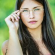Stock Photo: Young beautiful woman adjusts glasses