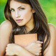Woman with bare shoulders holding brown book — Stock Photo