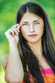 Young beautiful woman adjusts glasses — Stock Photo