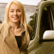 Young woman smiling about car — Stock Photo