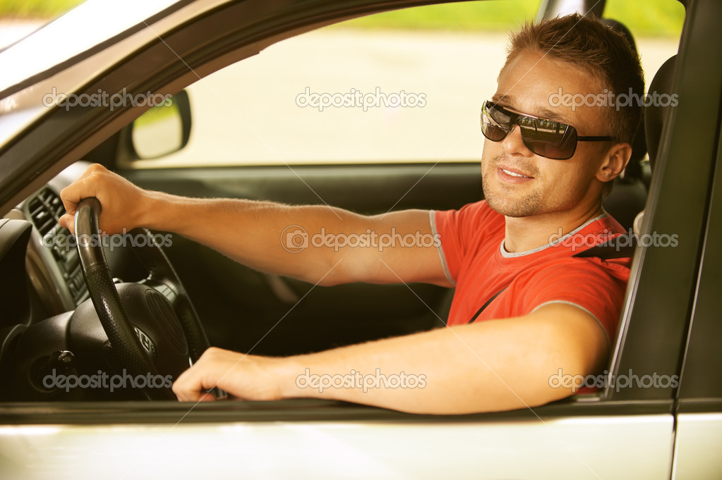 Portrait of beautiful young man in car smiles. — Stock Photo #10536084