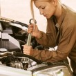 Young woman repairing car — Stock Photo