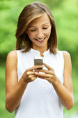 Young woman gathers message to mobile phone — Stock Photo