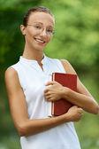 Kitap ile gözlüklü genç bir kadın — Stok fotoğraf