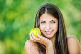 Woman with bare shoulders holding an apple — Stock Photo