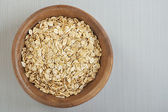 Rolled oats in a wooden bowl on a gray cloth. — Stock Photo