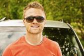 若い男の車について笑っています。 — ストック写真