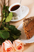 Bouquet of roses, piece of chocolate cake, a cup of tea, coffee — Stock fotografie