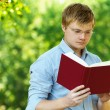 Student (male) with glasses reading book - Stock Photo