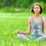 Woman meditating sitting on grass — Stock Photo