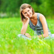 Woman sitting on green meadow with her legs crossed — Stock Photo