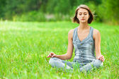 Woman meditating sitting on grass — Foto de Stock
