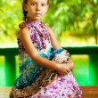 Girl sitting on wooden table — Stock Photo #8099237