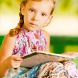 Girl sits reading book — Stock Photo