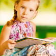 Stock Photo: Girl sits reading book