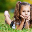 On grass is pretty sad little girl — Stock Photo