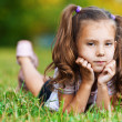 Stock Photo: On grass is pretty sad little girl
