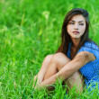 Sad woman sitting on grass — Stock Photo